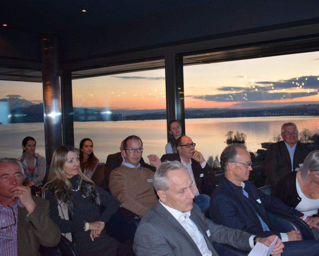 Die Teilnehmer hören der Referntin zu - Hintergrundstimmung Zugersee und Sonnenuntergang.